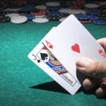 person-s-hand-holding-poker-card-casino_23-2147881370