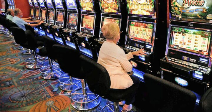 In this Thursday, Oct. 16, 2014 photo, a woman plays a video lottery terminal at Tioga Downs, in Nichols, N.Y.  New York regulators expected to soon hand out upstate casino licenses are looking no only at where gambling can make the most money, but where it can help the most.  (AP Photo/Mike Groll)