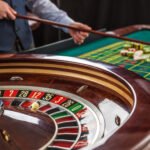 Roulette and piles of gambling chips on a green table in casino. Croupier collects chips using stick